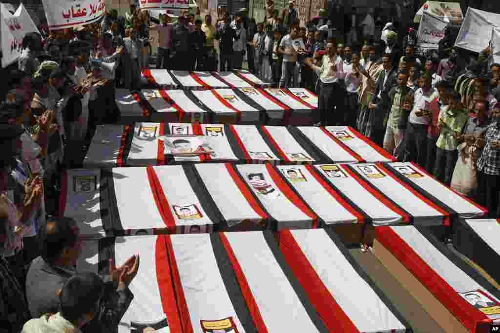Yemeni pro-democracy protesters pray around mock coffins in Sana'a.  They were remembering those who died on March 18, 2011, during a protest against Yemen's former president.