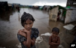 In this June 26, 2014 photo, a girl, self-identified as Rohingya, stands close to her family's tent house at Dar Paing camp for refugees, suburbs of Sittwe, Western Rakhine state, Myanmar.