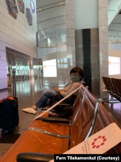 "Dunnapar ""Fern"" Tilakamonkul sat in a row of empty chairs at an airport in Doha, Qatar, during a 16-hour transit before flying to Iraq."