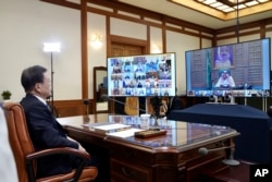 FILE - In this photo provided by South Korea Presidential Blue House via Yonhap News Agency, President Moon Jae-in attends G-20 virtual summit to discuss the coronavirus outbreak at the presidential Blue House in Seoul, March 26, 2020.