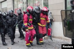 Firefighters carry police officer away from clashes during the traditional May Day protests, amid the coronavirus disease (COVID-19) outbreak in Paris, France, May 1, 2021.