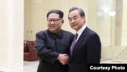 3일 김정은 북한 국무위원장(왼쪽)과 평양을 방문한 왕이 중국 외교담당 국무위원 겸 외교부장이 만나 악수하고 있다. 중국 외교부 사진 제공.