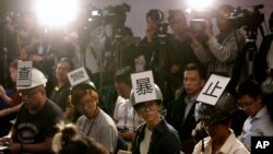 "Journalists wear helmets with signs that read; ""Investigate police brutality"" as they protest against alleged police violence towards reporters during a police press conference in Hong Kong, Monday, Nov. 4, 2019."