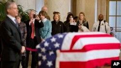 Miembros del público tomaron fotografías en sus teléfonos celulares mientras observaban el féretro del juez Antonin Scalia en el salón principal de la Corte Suprema en Washington, el viernes, 19 de febrero de 2016.