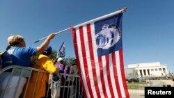 Seorang peserta pawai melmegang bendera Amerika bergambarkan Presiden Obama dalam peringatan 50 Tahun Pawai Washington di Monumen Lincoln, Washington (24/8). Presiden Obama akan menyampaikan pidato utama dalam puncak peringatan peristiwa bersejarah perjuangan hak sipil di monumen ini, Rabu (28/8).