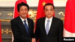 日本首相安倍晉三在東京與到訪的中國總理李克強握手。(2018年5月9日)