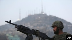 FILE - An Afghan soldier stands guard in Kabul.