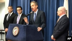 Los Angeles City Attorney Mike Feuer, at podium, speaks at a news conference in Los Angeles, Jan. 4, 2019. Feuer said that owners of The Weather Channel app used it to track people's every step and profit off that information.