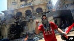 1일 무슬림형제단 본사 건물을 공격한 이집트 반정부 시위대 일원이 이집트 국기를 손에 쥐고 있다.