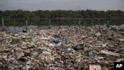 In this May 15, 2014 photo, trash floats on a polluted waterway that flows into the Guanabara Bay in Rio de Janeiro, Brazil.
