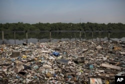 FILE - In this May 15, 2014 photo, trash floats on a polluted water channel that flows into the Guanabara Bay in Rio de Janeiro, Brazil.