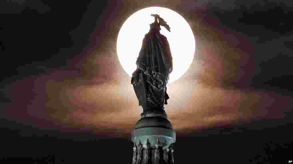 A supermoon rises through the clouds behind the bronze Statue of Freedom atop the U.S. Capitol, Washington, DC, Aug. 10, 2014.