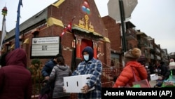 People receive free food from the United Sherpa Association's weekly food pantry on Friday, January 15, 2021, in Queens, New York. (AP Photo/Jessie Wardarski)