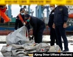 Anggota tim penyelamat membawa puing-puing pesawat Sriwijaya Air penerbangan SJ182 yang jatuh ke laut, di pelabuhan Terminal Peti Kemas Internasional Jakarta, 10 Januari 2021. (Foto: REUTERS/Ajeng Dinar Ulfiana)