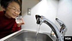 Seorang warga Tokyo meminum air ledeng langsung dari keran.