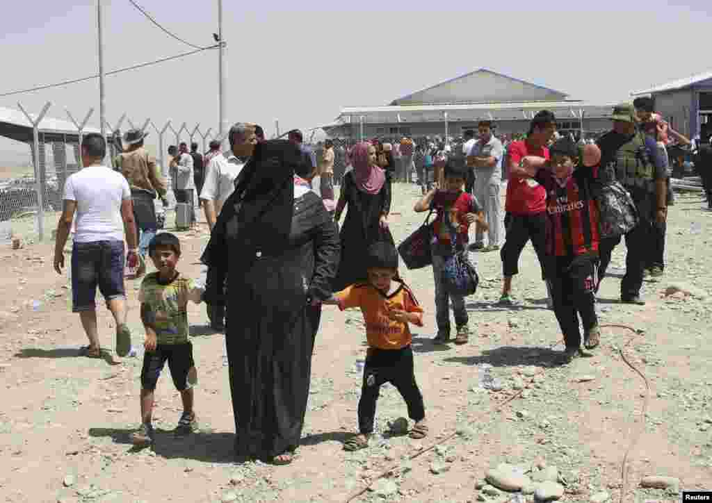 Families fleeing the violence in Mosul wait at a checkpoint on the outskirts of Irbil, Iraq, June 10, 2014.