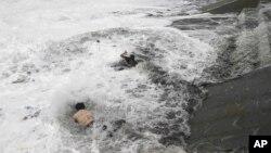 Người đàn ông nhảy xuống nước để cứu một phụ nữ bị rời xuống nước vì các đợt sóng lớn trên Vịnh Bengal, Ấn Độ khi bão ập vào hôm Chủ nhật, 12/10/14