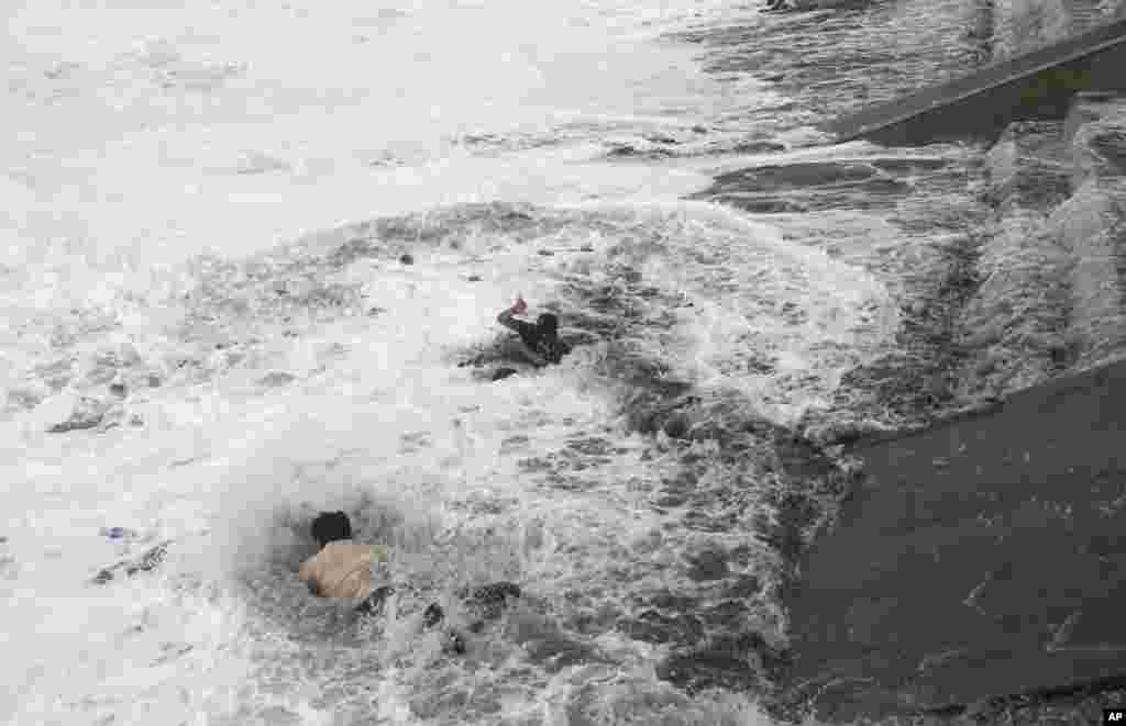 대형 허리케인에 인도 북부를 강타한 가운데, 오리사에서 한 남성이 강한 파도에 휩쓸려 물에 빠진 여성을 구하고 있다.