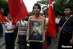 People hold General Aung San's portrait as they wait to pay respect during an event marking the anniversary of Martyrs' Day outside the Ministers' Building, formerly known as the Secretariat building, in Yangon, Myanmar, July 19, 2015.
