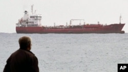 """A man looks at the Saint Vincent-flagged """"Chariot"""" cargo ship as it sails out of the port of the southern Cypriot city of Limassol, January 11, 2012."""