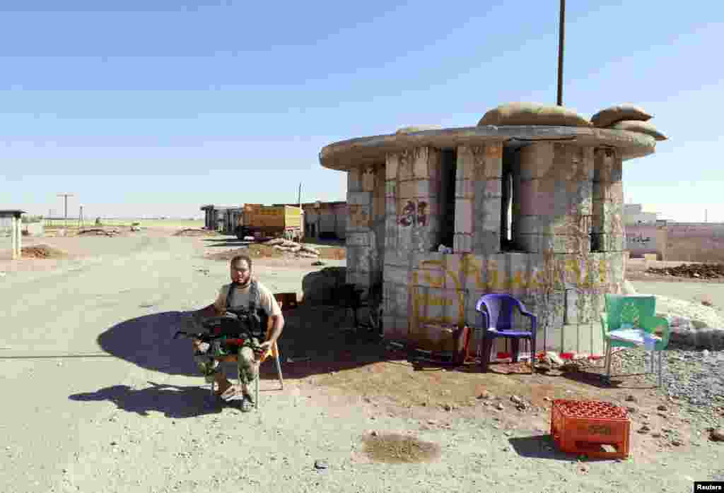 An Islamic State fighter sits at a checkpoint once used by Kurdish fighters in al-Jurn village, Oct. 7, 2014.