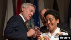 Secretary of the Navy Ray Mabus, left, puts four-star shoulder boards on Admiral Michelle Howard's uniform during her promotion ceremony at the Women in Military Service for America Memorial, Arlington, Virginia, July 1, 2014.