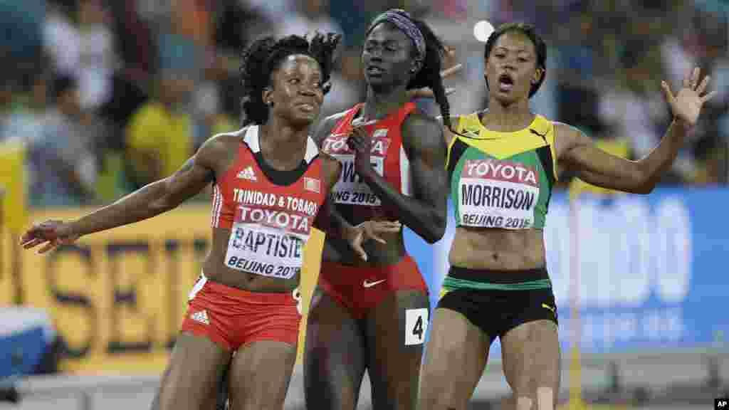 Kelly-Ann Baptiste de Trinité-et-Tobago, à gauche, entre en collision avec Tori Bowie des États-Unis et Natasha Morrison de la Jamaïque, à droite, au terme leurs course de 100m de démi-finales des championnats du monde d'athlétisme au stade Nid d'oiseau à Pékin, 24 août 2015.
