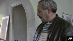 ពលរដ្ឋទុយនេស៊ីម្នាក់កំពុងពិនិត្យមើលគោមគ្របអំពូលមួយដែលលោកបានរកឃើញក្នុងពេលលោកដើរមើលនៅក្នុងភូមិគ្រឹះរបស់ក្រុមគ្រួសារអតីតប្រធានាធិបតីផ្តាច់ការទុយនេស៊ី ហ្ស៊ីន អិល អាប៊ីឌីន បិន អាលី (Zine el Abidine Ben Ali) កាលពីខែមករាឆ្ន