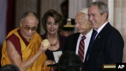 The Dalai Lama, left, holds up the Congressional Gold Medal during a ceremony in the Capitol Rotunda on Capitol Hill in Washington, Wednesday, Oct. 17, 2007. Looking on, from second from left are, House Speaker Nancy Pelosi of calif., Sen. Robert Byrd, D-