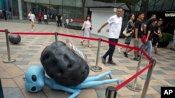 在北京一個受歡迎的零售區,購物者走過一個表現外星人被隕石砸倒的雕塑,這是個吸引顧客目光的促銷噱頭(2018年7月13日)。