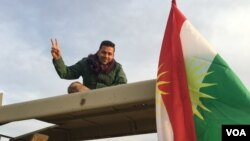 """Seorang tentara Kurdi Peshmerga mengacungkan tanda """"V"""" (victory atau kemenangan) ketika pasukan Irak mulai memasuki desa-desa yang dikuasai ISIS di Mosul, Kamis (24/3)."""