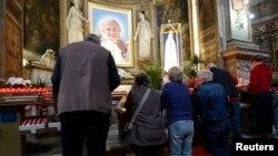 Católicos oran en una iglesia en Roma frente a una imagen del papa Juan Pablo II.