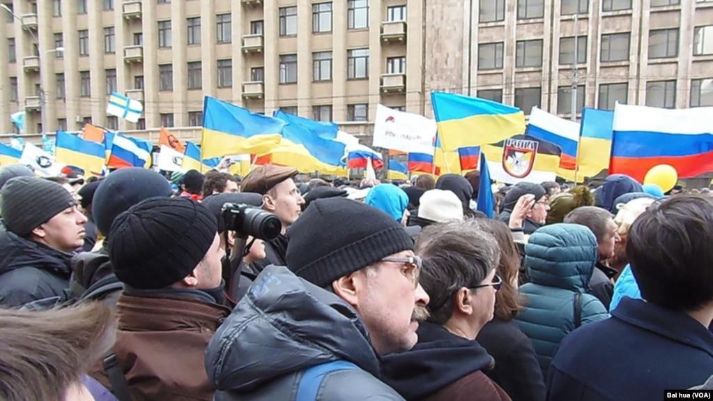在2014年3月15日的莫斯科大規模示威遊行中,人們抗議俄羅斯吞併克里米亞並支持烏克蘭,集會現場可看到許多烏克蘭國旗。 (美國之音白樺拍攝)