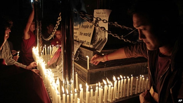 Exiled Tibetans light candles in front of portraits of 16-year-old monk Phuntsog, during a candlelit vigil to honor the monk who set himself on fire in an anti-government protest, in Dharmsala, India, March 16, 2011