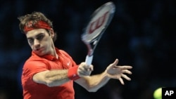 Switzerland's Roger Federer plays a return to Serbia's Novak Djokovic during a semifinal single tennis match of the ATP World Tour Finals at O2 Arena in London, Saturday, Nov. 27, 2010. (AP Photo/Sang Tan)