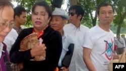 Chị Bùi Minh Hằng ôm chiếc nón 'Hoàng Sa-Trường Sa-Việt Nam' sau cuộc giằng co với lực lượng đeo băng đỏ