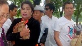 Chị Bùi Thị Minh Hằng ôm chiếc nón 'Hoàng Sa-Trường Sa-Việt Nam' sau cuộc giằng co với lực lượng đeo băng đỏ
