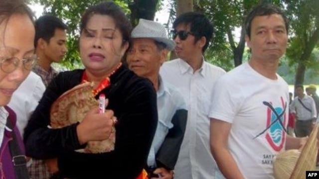 """Chị Bùi Thị Minh Hằng bị giật rách chiếc nón có ghi dòng chữ  """"Hoàng Sa-Trường Sa-Việt Nam"""" trong một cuộc tuần hành chống Trung Quốc tại Hà Nội"""