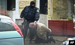 Teodor Chetrus is detained by a police officer in Chisinau, Moldova during a uranium-235 sting operation, June 27, 2011.