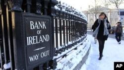 Seorang perempuan tengah melintas di depan kantor cabang Bank Irlandia di Central Dublin (Foto: dok). Para ahli ekonomi dan kelompok bisnis Irlandia menyerukan agar pemerintah melonggarkan program penghematan.