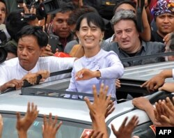 Aung San Suu Kyi (au c.) salue la foule après un discours à Rangoon (2 avril 2012)