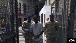 Seorang tahanan dikawal petugas keamanan di penjara militer AS di Guantanamo, Kuba.