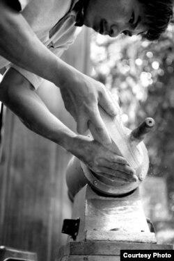 Một người thợ mộc đang bào một miếng gỗ tạo hình đôi guốc