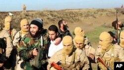 Hình ảnh cho thấy các phiến quân Nhà nước Hồi giáo bắt được phi công người Jordan (áo trắng) tại Raqqa, Syria, ngày 24/12/2014.