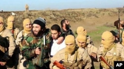 An image from Raqqa Media Center of the Islamic State group, which has been authenticated based on its contents and other AP reporting, shows Islamic State fighters with what is believed to be a captured pilot, center, in a white shirt, in Raqqa, Syria, Dec. 24, 2014.