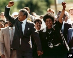 FILE – Nelson Mandela and wife Winnie Madikizela-Mandela raise clenched fists as they walk hand-in-hand upon his release from prison in Cape Town, South Africa, Feb. 11, 1990.