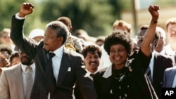FILE - In this Feb. 11, 1990 file photo, Nelson Mandela and his wife, Winnie Madikizela-Mandela, raise clenched fists as they walk hand-in-hand upon his release from prison in Cape Town, South Africa. (AP Photo/Greg English, File)