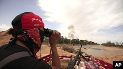 A Libyan rebel fighter uses a pair of binoculars as smoke rises from an explosion at Misrata's western front line June 11, 2011. The cause of the explosion was unclear.
