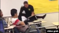 FILE - An image from video shows Spring Valley High School (Columbia, S.C., student resource officer Ben Fields, a senior deputy with the Richland County police department, using force to remove a female student from a classroom, Oct. 26, 2015.