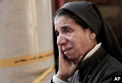 FILE - An Egyptian Coptic nun weeps as she looks at damage inside the St. Mark Cathedral in central Cairo, following a bombing,Dec. 11, 2016.